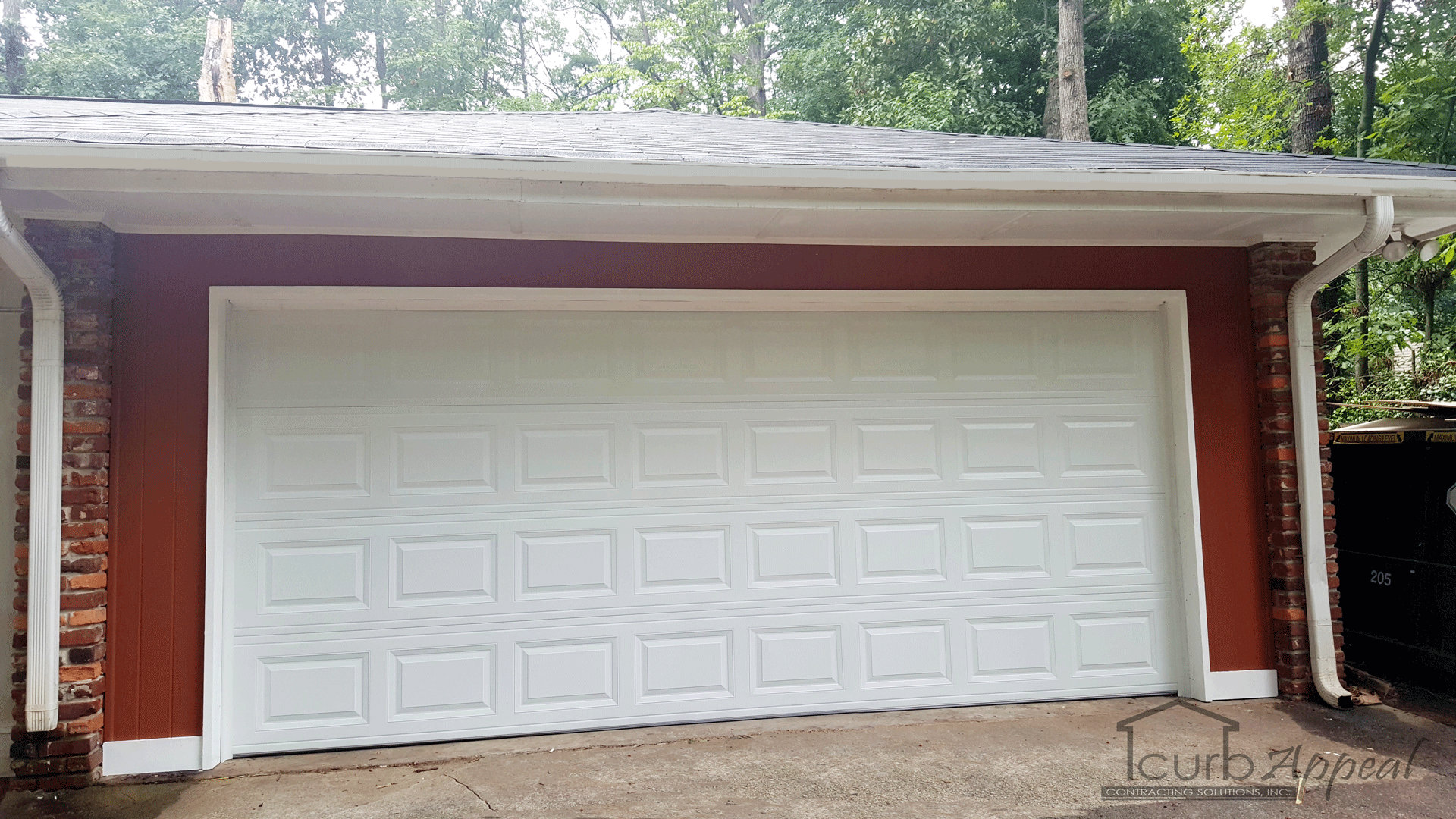 A white garage door installed after converting a carport into a garage.