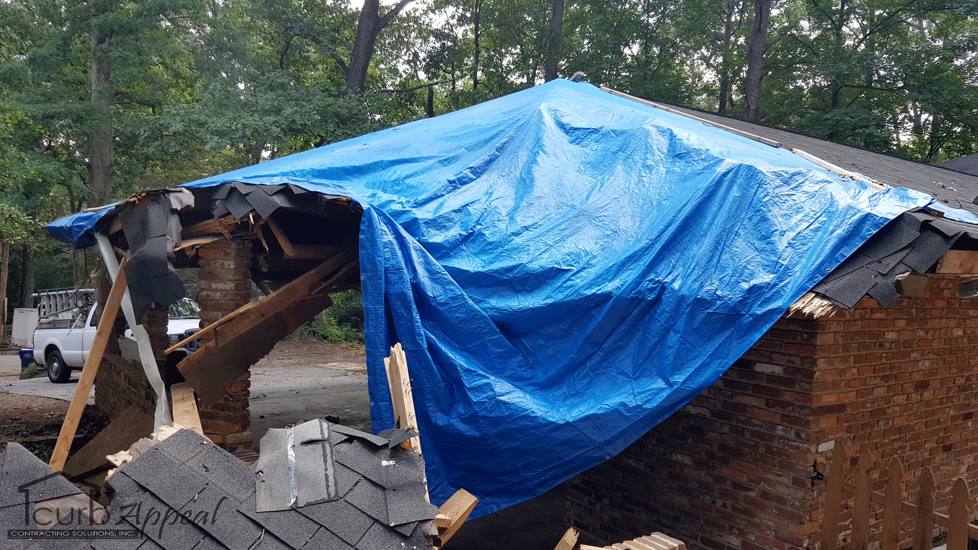 A tarp covers the remains of a carport destroyed by a falling tree.