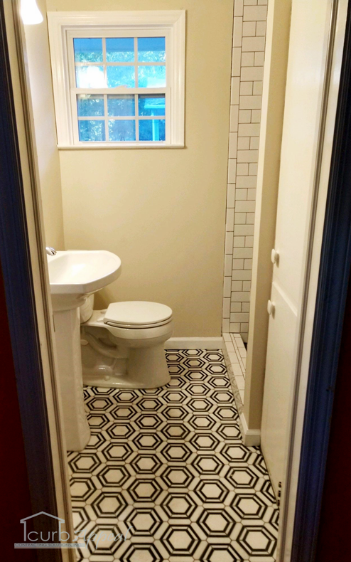 New black and white motif tile floor, shower, and new sinks/toilets after a bathroom remodel.