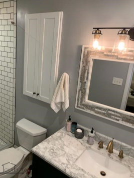 A marble vanity top, tile frame mirror, and white cabinetry in Buford, GA.