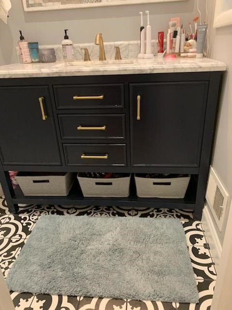 A navy vanity with brass hardware in a bathroom.