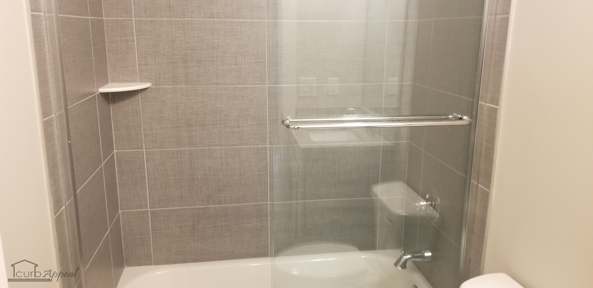 A bathtub with tiled walls and a frameless shower door in Buford, GA.